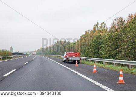 Faulty Car With Red Trailer And Traffic Cones On Emergency Stopping Lane On Roadside. Problem With V