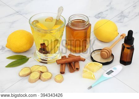 Healthy food for cold, cough & flu remedy with digital thermometer, essential oil, hot drink of honey, lemon, ginger & cinnamon spice on marble high in antioxidants & vitamin c. Health care concept.