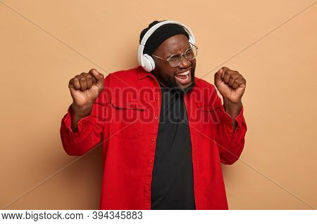 Overjoyed Black Bearded Man Raises Clenched Fists, Sings Song Aloud, Dances And Enjoys Music, Wears