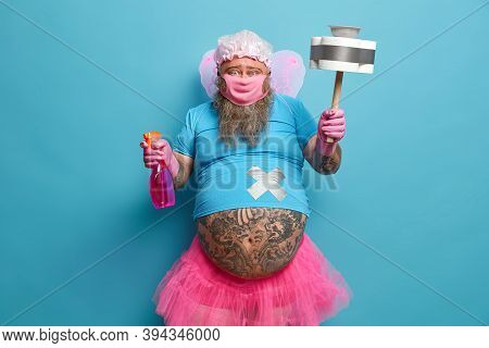 Male Cleaning Fairy Has Big Belly Poses With Detergent And Cleaning Tool, Wears Mask And Rubber Glov