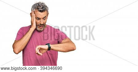 Middle age grey-haired man wearing casual clothes looking at the watch time worried, afraid of getting late