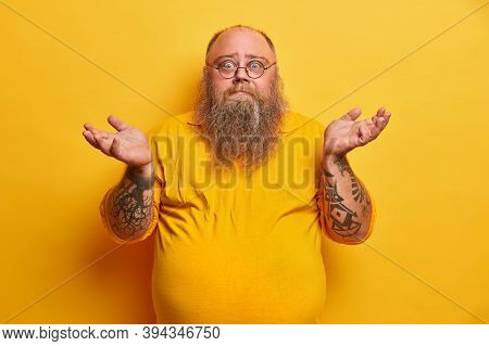 Indoor Shot Of Hesitant Bearded Man With Excess Weight Shrugs Shoulders And Stands Unaware, Has Thic