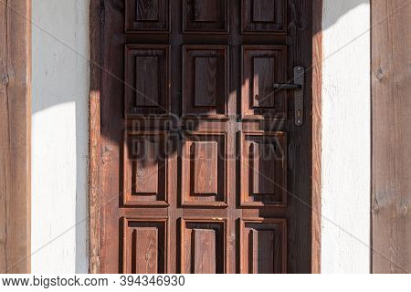 Dark Wooden Door With New Metal Handle Outdoor Lit By Warm Sunray On Sunny Autumn Day
