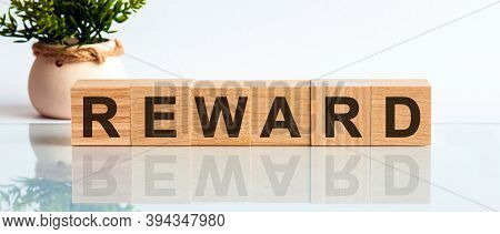 Wooden Blocks With The Text: Reward. The Text Is Written In Black Letters And Is Reflected In The Mi
