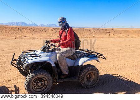 Young Man In Safari Trip Through Egyptian Desert Driving Atv. Quad Bikes Safari In The Desert Near H