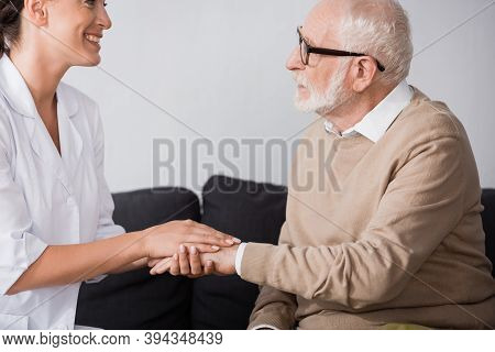 Side Of Aged Man In Eyeglasses Holding Hands With Social Worker At Home