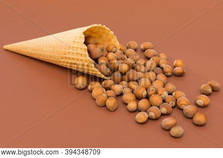 Hazelnuts Pour Out Of The Waffle Cone. The Idea Is That The Ice Cream Contains Natural Ingredients,