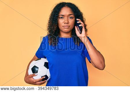 Young african american woman holding football ball talking on the smartphone relaxed with serious expression on face. simple and natural looking at the camera.