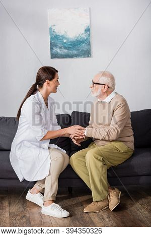 Side View Of Nurse And Aged Man Talking While Sitting On Sofa