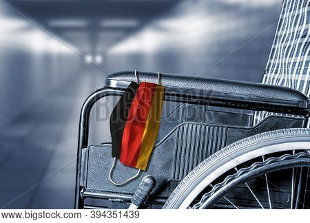 Flag Of Germany On Face Mask Hanging On Empty Wheelchair In Hallway Of Hospital Or Retirement Nursin