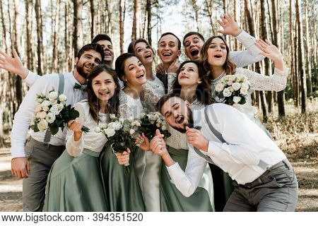 Group Of Young People Hugging Tightly And Laughing Cheerfully,a Group Of Friends Celebrating A Weddi