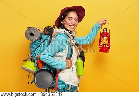 Isolated Shot Of Cheerful Woman Trekker Holds Kerosene Lamp, Wears Hat And Casual Wear, Going Have R