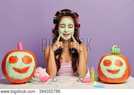Portrait Of Pleased Young Woman Keeps Both Fore Fingers On Face, Shows Natural Clay Mask, Wears Hair