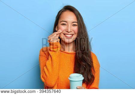 Pretty Brunette Asain Millennial Woman Holds Takeaway Coffee Cup, Enjoys Drink During Break, Wears W