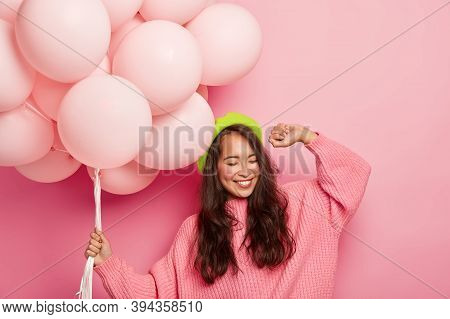 Overemotive Chilling Woman With Cheerful Expression, Raises Hand, Dances To Music, Has Fun At Party,