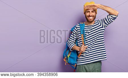 Happy Smiling Hipster Guy Keeps Palm Near Forehead, Looks Gladfully Into Distance, Carries Big Rucks