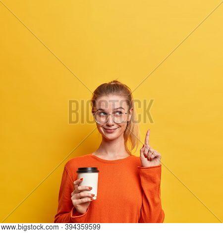 Vertical Shot Of Happy Pleased European Woman Wears Casual Orange Jumper, Transparent Glasses, Point