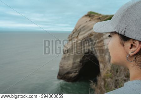 Close Up Of Woman Face At Amazing Cliff Landscape At Cape Farewell, New Zealand.