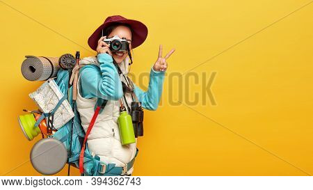 Photo Of Active Female Model Makes Shots On Retro Camera, Shows Peace Gesture, Dressed In Casual Clo