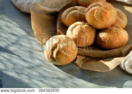 Kaiser, Or Vienna Buns In Bread Basket On On Dark Grey Background With Yellow Autumn Leaves.