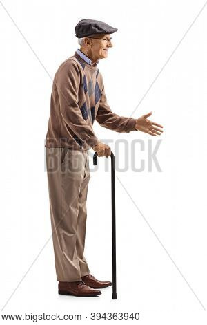 Full length profile shot of an elderly man with a walking cane greeting with hand isolated on white background