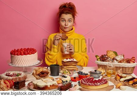 People, Nutirtion, Calories, Bakery Concept. Ginger Girl In Yellow Jumper Eats Tasty Oatmeal Cookies