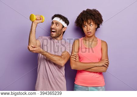 Athletic Man Lifts Dumbbell, Has Weary Workout, Wears Headband And T Shirt, Unhappy Bored Woman Stan