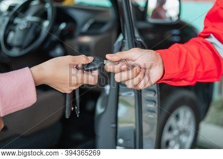 Close Up Of Customer Hand Giving Car Keys To Mechanic