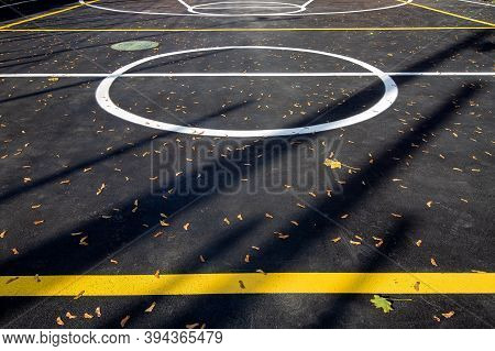 Basketball Area In Circle On The Marking Playing Field With Asphalt Tarmac, Sports  Lit By Sun Light