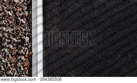 Side Of An Asphalt Bituminous Road With A Curb And Mulching With Crushed Stone, Texture Tarmac Road