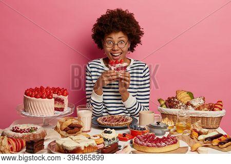 Joyful Afro American Woman Bites Delicious Creamy Cake, Tastes Various Desserts, Has Sweet Tooth, Ca