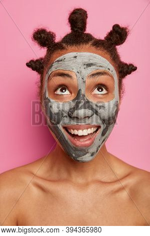 Happy Positive Woman Looks Upwards, Applies Purifying Facial Mask, Removes Blackheads, Looks Curious