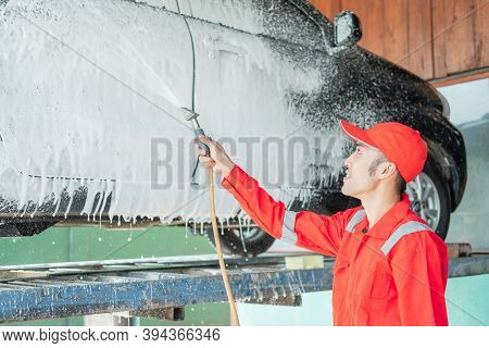 Male Car Cleaner Wearing A Red Uniform And A Hat Is Spraying Snow Foam On The Car Door
