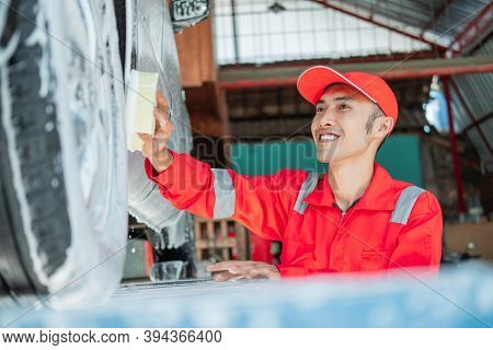 Male Car Cleaner Wears Red Uniform And Smiling Hat While Washing Car With Foamy Sponge