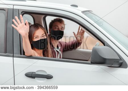 Happy driver and passenger waving hello driving new car on road trip or drivers license test at school.
