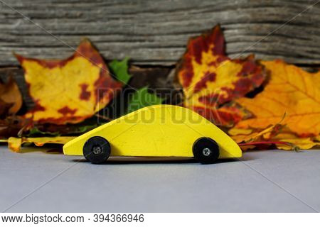 Yellow wooden toy car with cloorful leaves and wood in back