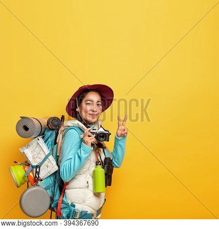 Vertical Image Of Active Female Traveler Makes Peace Gesture, Holds Retro Camera For Taking Pics, Ca