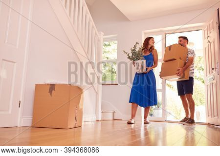 Mature Couple Carrying Boxes Through Front Door Into New Home On Moving Day