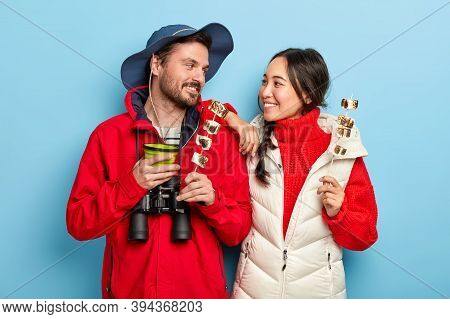 Cheerful Woman And Man Have Camping Trip Together, Hold Tasty Marshmallow Made On Bonfire, Look With