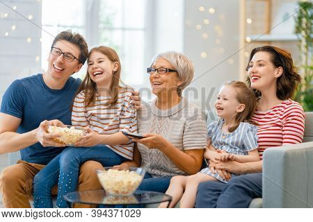 Happy family watching TV with popcorn  at home. Granny, mother, father and daughters spending time together.