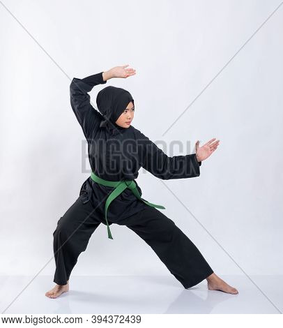 Asian Women In Hijabs Wearing Pencak Silat Uniforms With Green Belts Perform Stance Movements