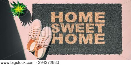 Home sweet home doormat. Homeowner moving in new house concept with top view of pink shoes and entrance door mat. Panoramic banner background.