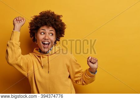Photo Of African American Girl Does Lucky Dance, Raises Hands Up In Hooray, Feels Like Champion Afte