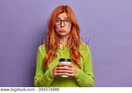 Miserable Dissatisfied Offended Young Woman Looks With Gloomy Expression At Camera, Holds Cup Of Cof