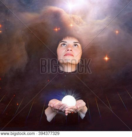 A Girl In Black Clothes Holds A Shining Ball In Her Hands And Looks Up At The Dramatic Sky. The Conc