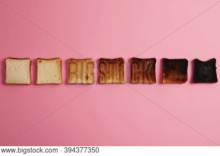 Slices Of Bread At Different Stages Of Toasting. Crunchy Toasted Slices Arranged In One Row Over Pin