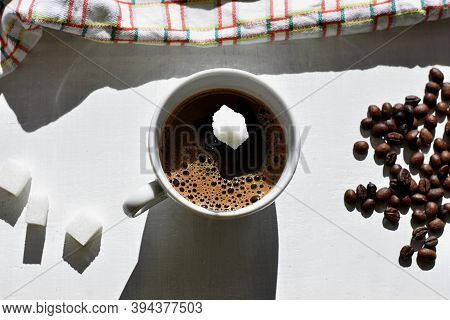 Sugar Cube Falling Into A Cup Of Coffee/a Sugar Cube Dropped Into A Cup With Black Coffee. Falling S