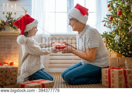 Merry Christmas and Happy Holidays! Cheerful grandma and her cute grand daughter girl exchanging gifts. Granny and little child having fun near tree indoors. Loving family with presents in room.