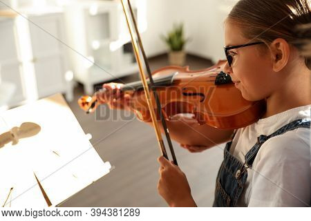 Cute Little Girl Playing Violin Indoors, Closeup. Music Lesson