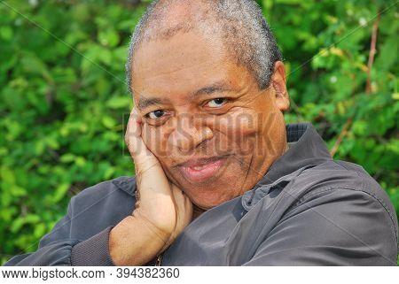 African American Male Expressions Sitting On A Park Bench Alone Outside.